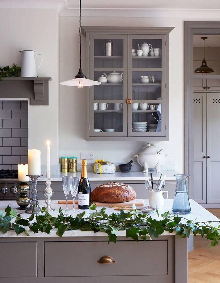 зелёная гирлянда и свечи на новогоднем украшении кухни