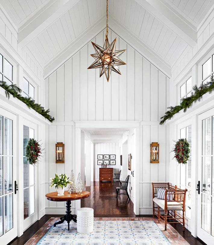 белый интерьер дома, обшитый досками украшен живой хвоей