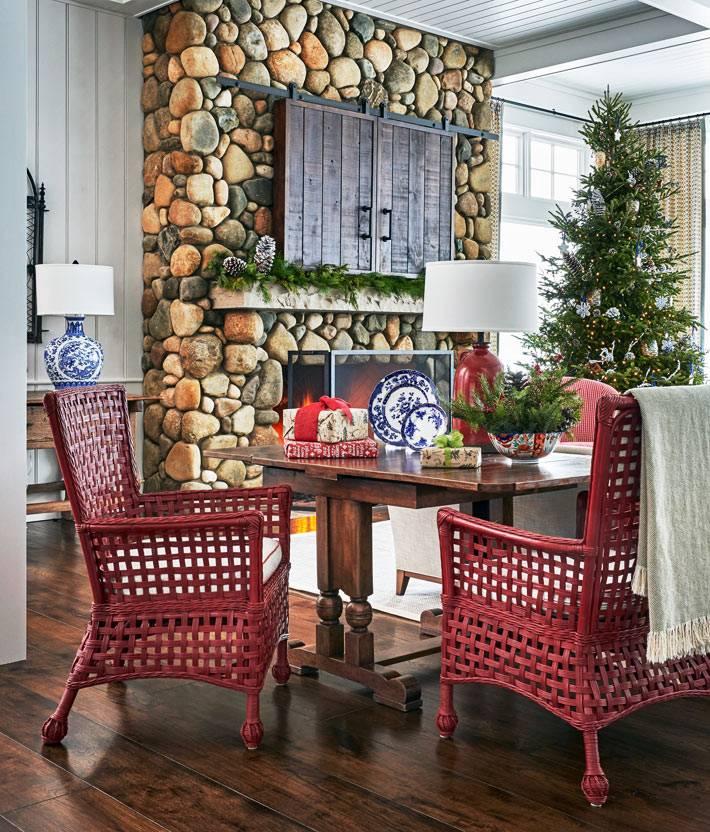 красный плетеные кресла за обеденным столом возле камина с живым огнем