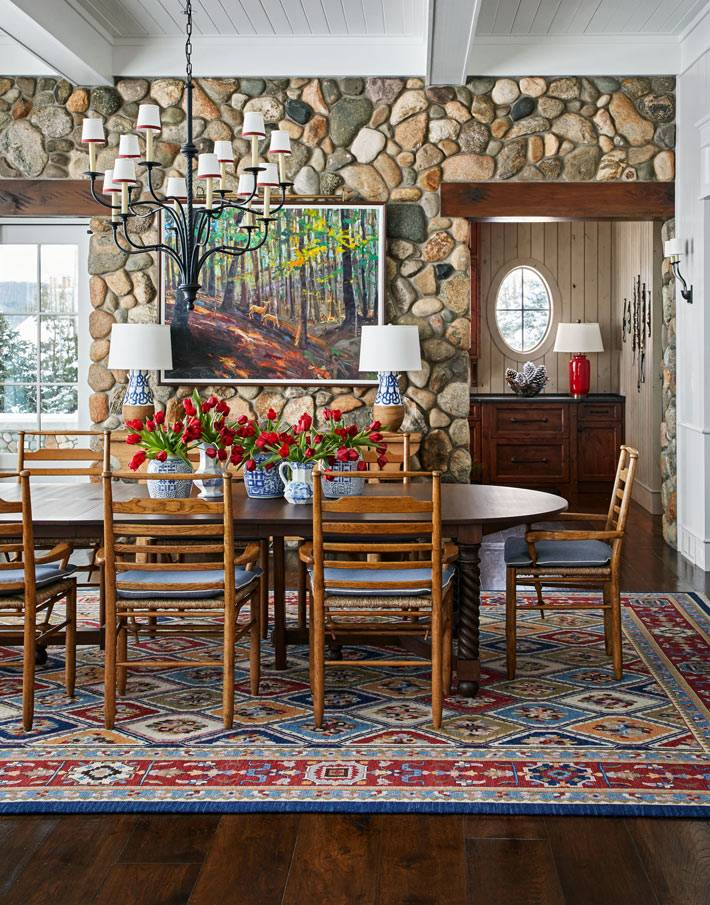 стены в столовой выложены морским камнем, на полу красивый ковер