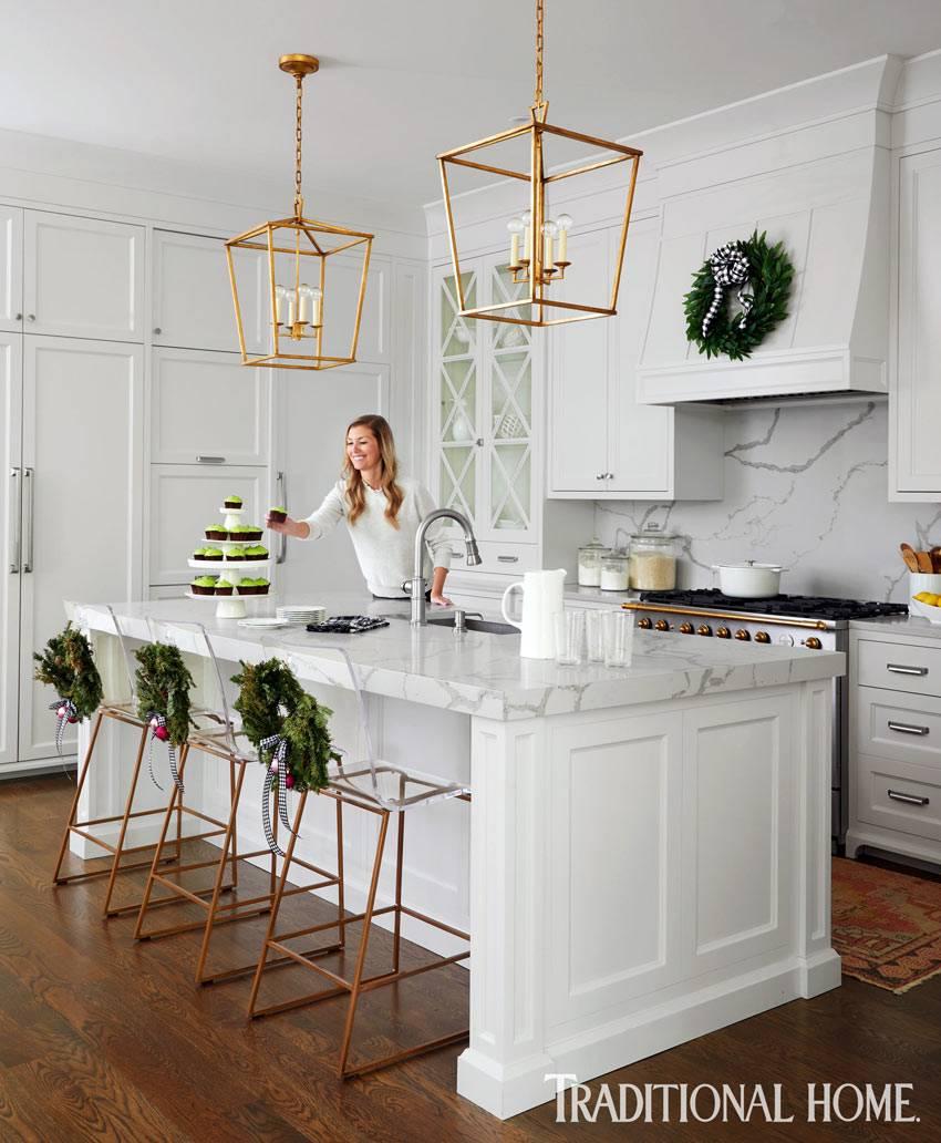 белая мебель на кухне с паркетным полом, золотистые люстры