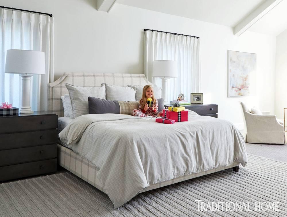 большая спальня с белой кроватью и прикроватным комодом