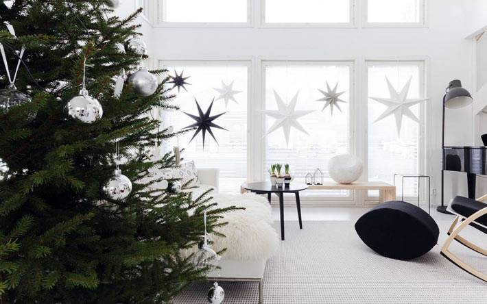много бумажных звёзд на окне в белом интерьере фото