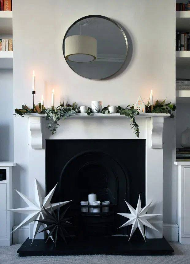черный камин с белым порталом, свечи внутри камина