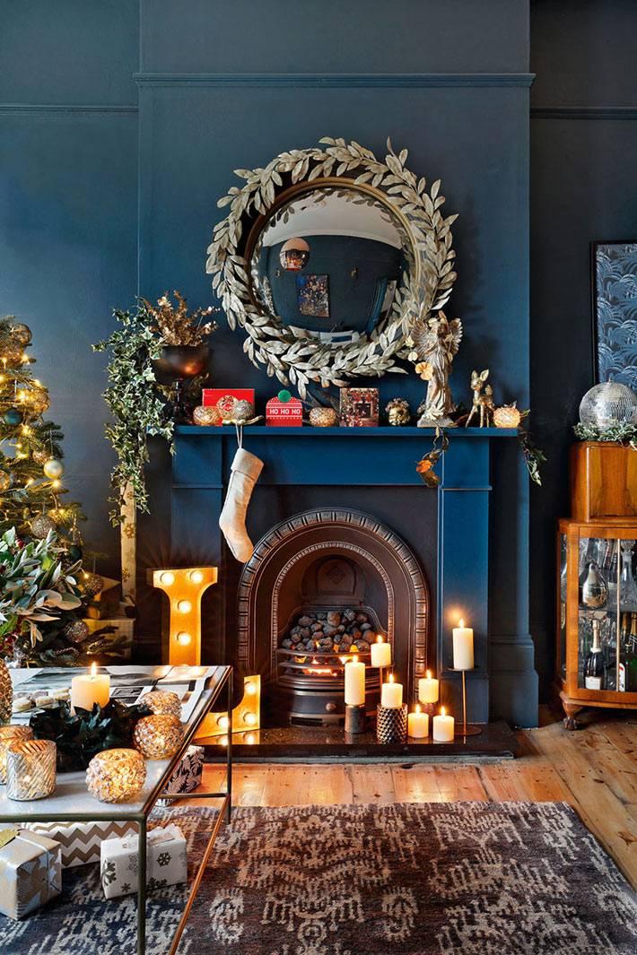 комната с синими стенами, камин со свечами. новогоднее украшение
