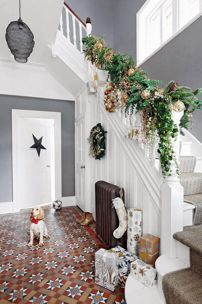 новогодняя гирлянда на перилах лестницы в холле дома