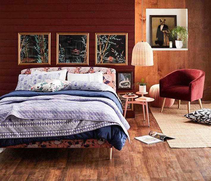 уютная спальня с деревянными стенами и бордовым креслом