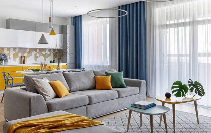 серый диван как разделитель между кухней и гостиной