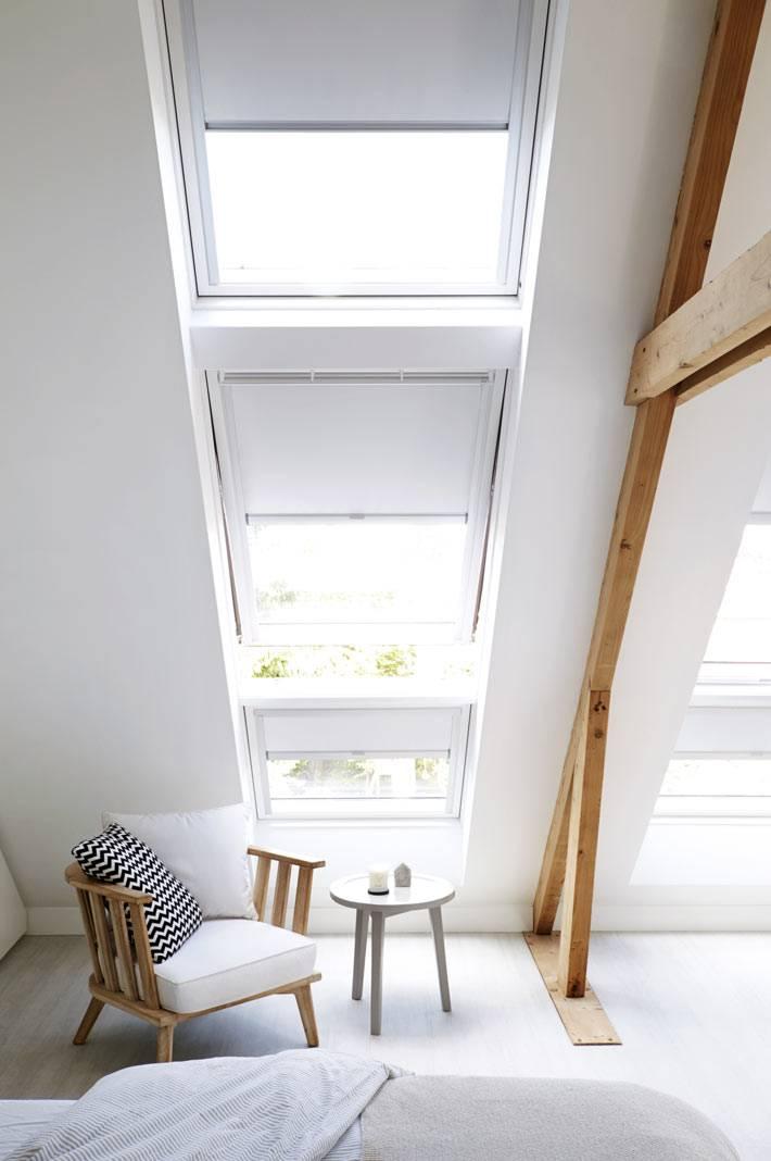 стильное кресло с деревянным каркасом и белыми подушками