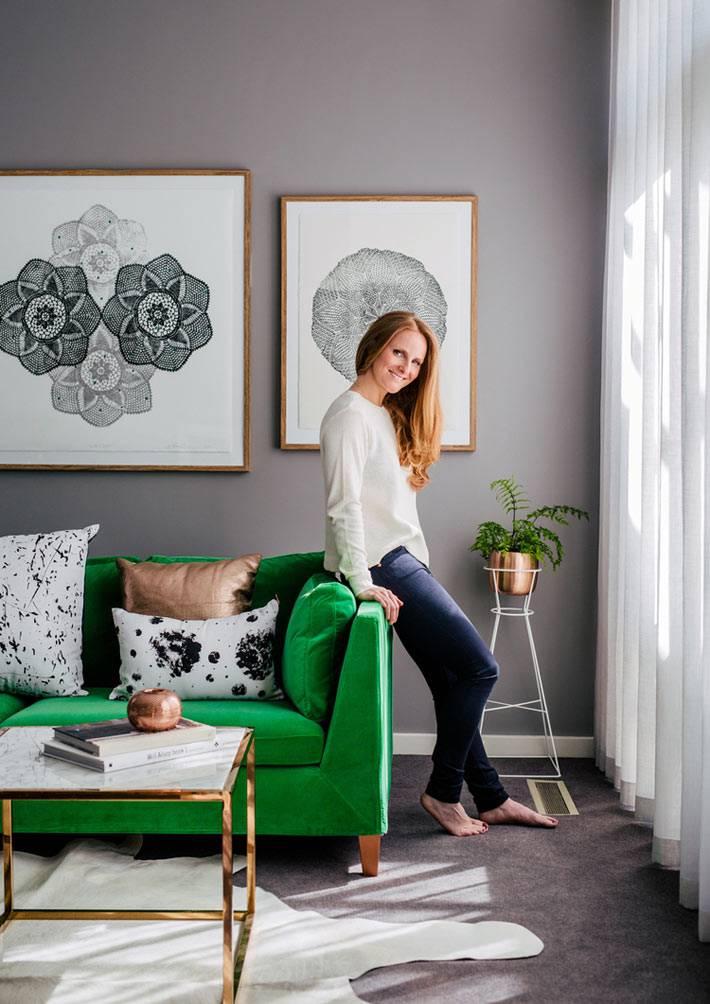 зеленый диван в комнате с серыми стенами и большим окном