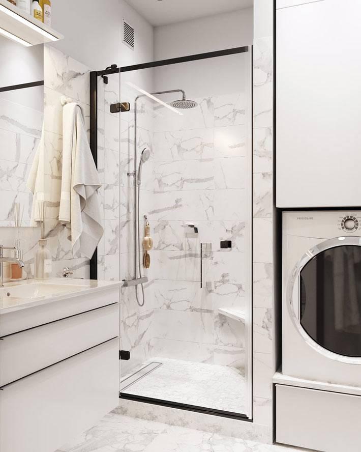 душевая кабина за стеклом и зона для стирки в маленькой ванной