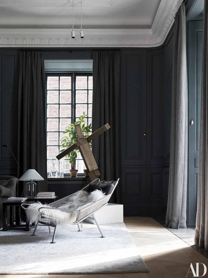 комната с темными стенами и черными шторами на окне