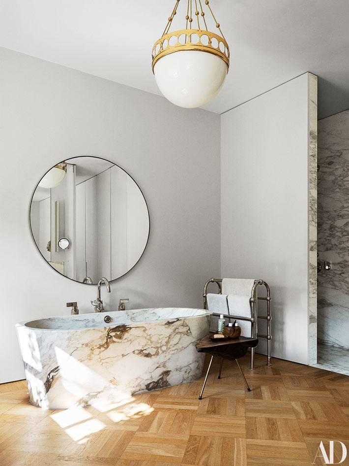 овальгая чаша ванны из мрамора, круглое зеркало над ванной