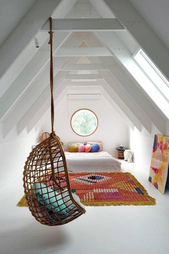белое пространство мансардной комнаты с ярким ковром