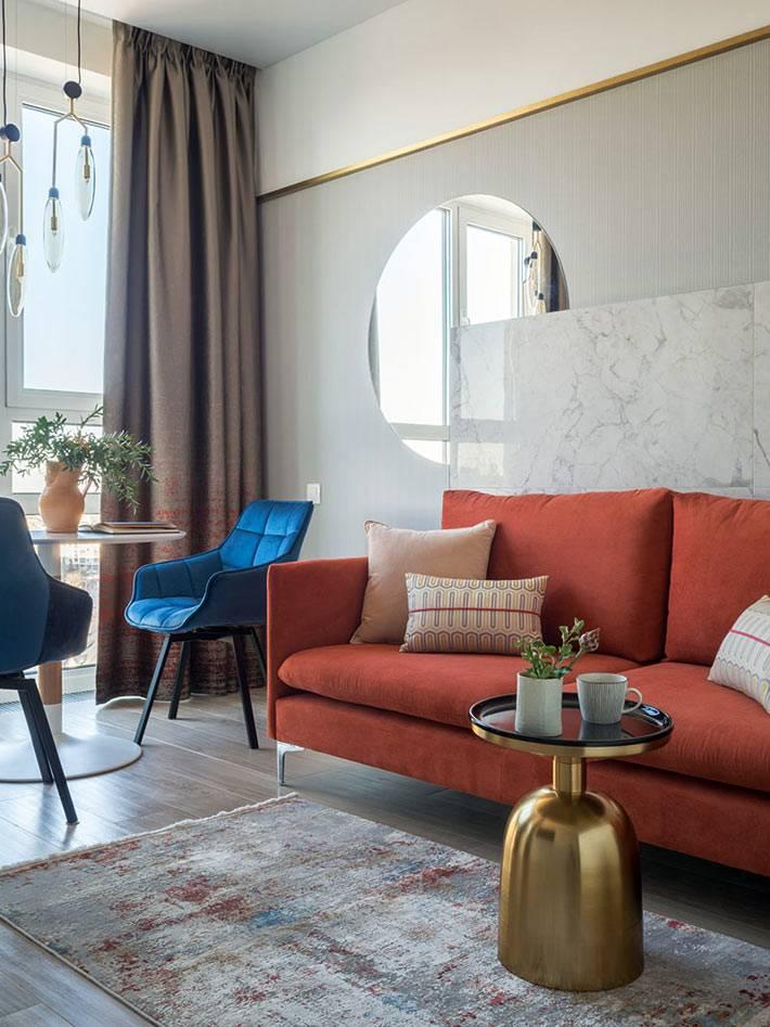 красный диван и синие кресла в комнате, золотистый столик