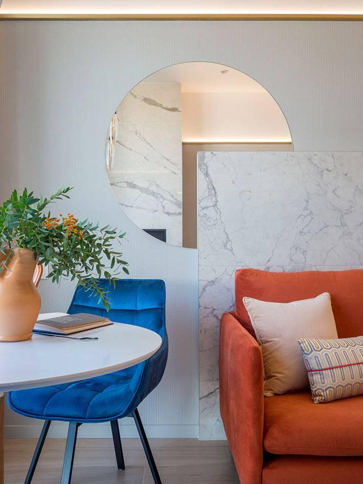 большое круглое зеркало на стене над диваном