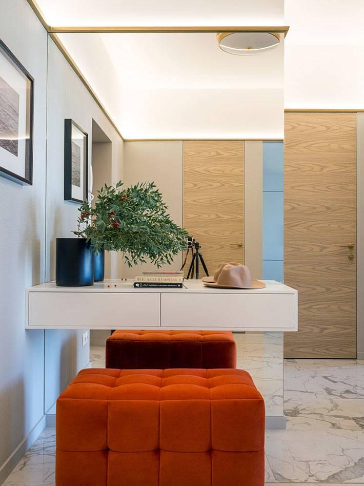 минималистичная прихожая с большим зеркалом и оранжевым пуфом