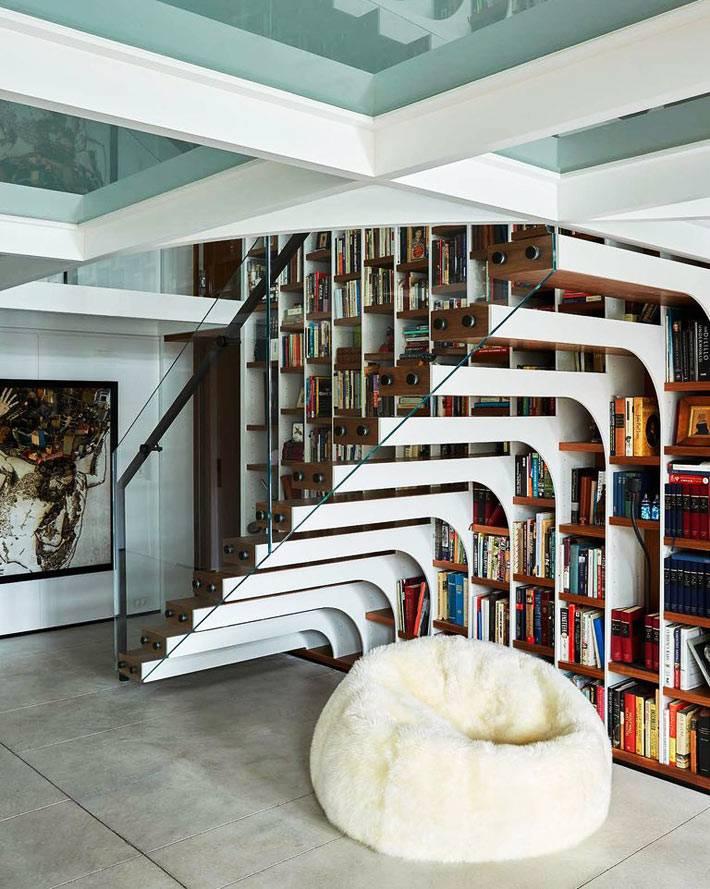 лестница со стеклянными перилами возл стеллажй с книгами