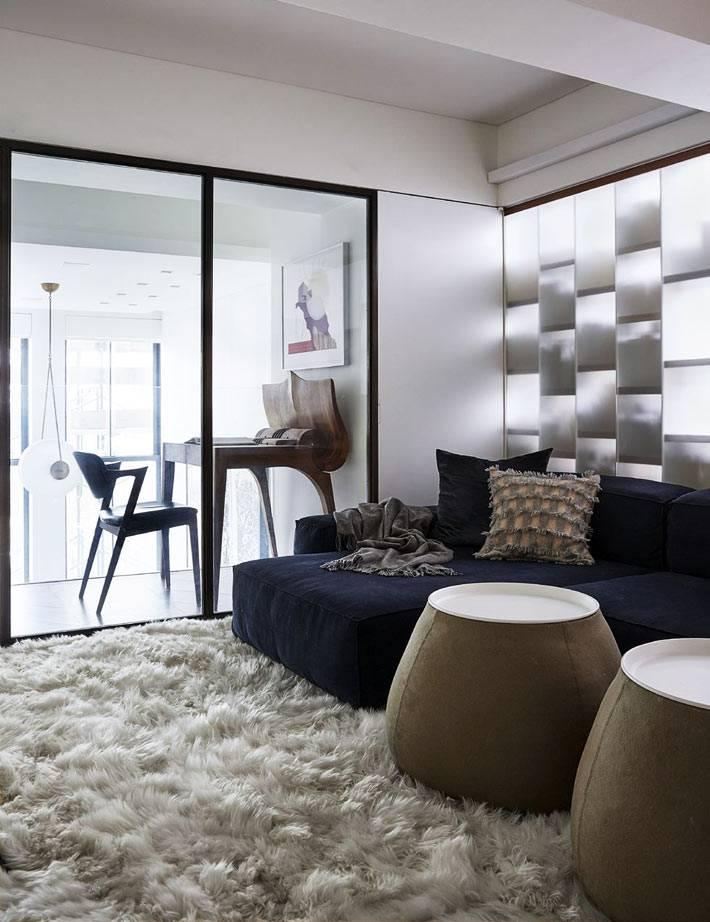 уютная комната с пушистым меховым ковром на полу и синим диваном