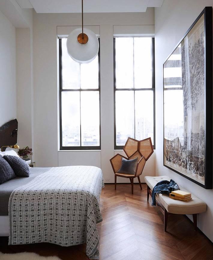спальня с высокими потолками и большими окнами без штор