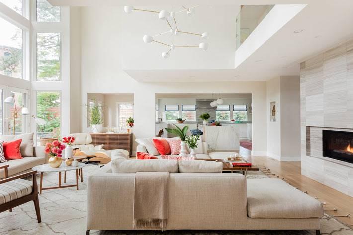 белое пространство гостиной с красными подушками и цветами
