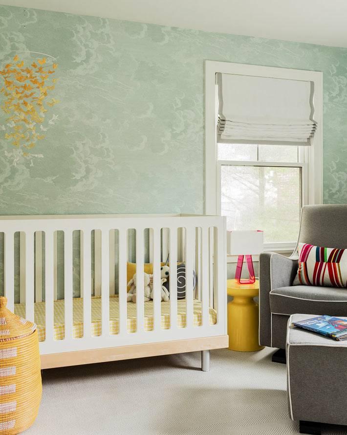 детская для младенца с бледно-зелеными стенами и желтым декором