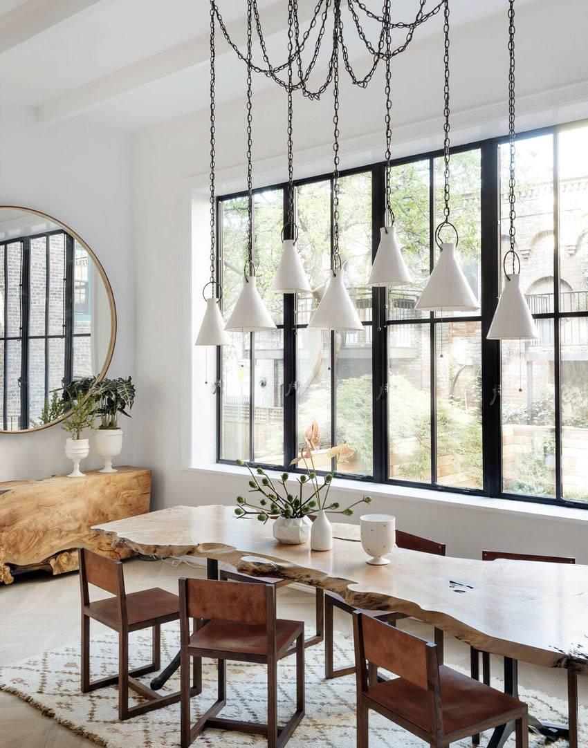 обеденный стол из обработанного спила дерева, лампы на подвесах