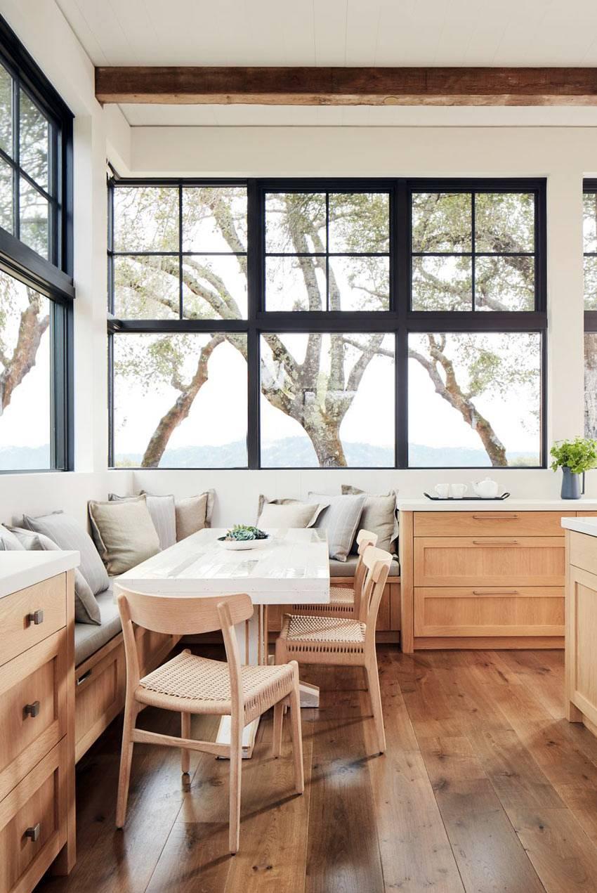 мягкая лавка и окна с черной рамой в уголке для завтраков