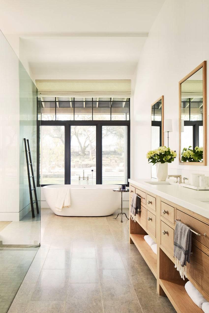чаша ванной стоит перед большим окном с красивым видом