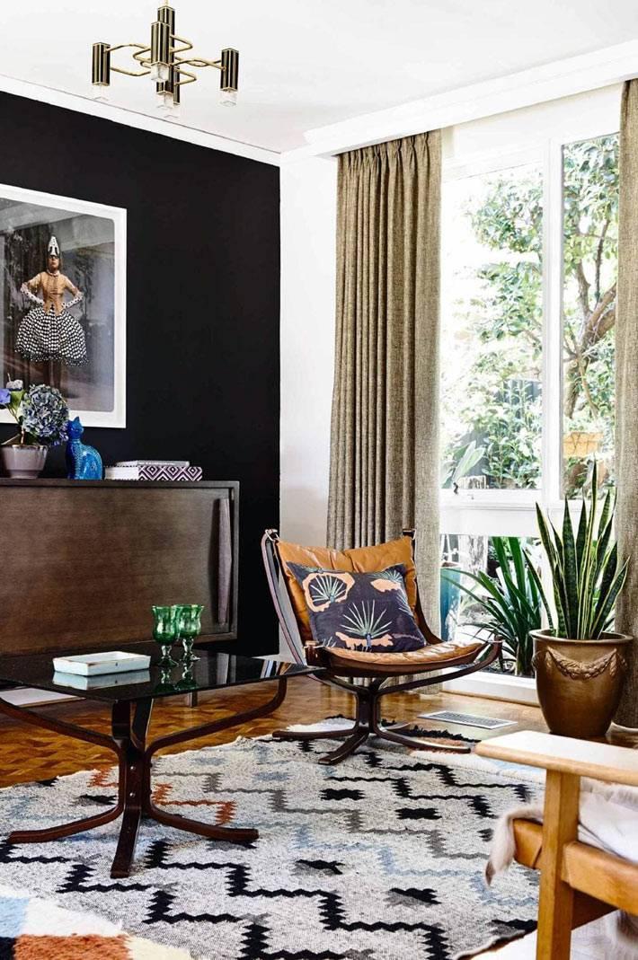 колоритный дизайн гостиной с кожаным креслом и черной стеной