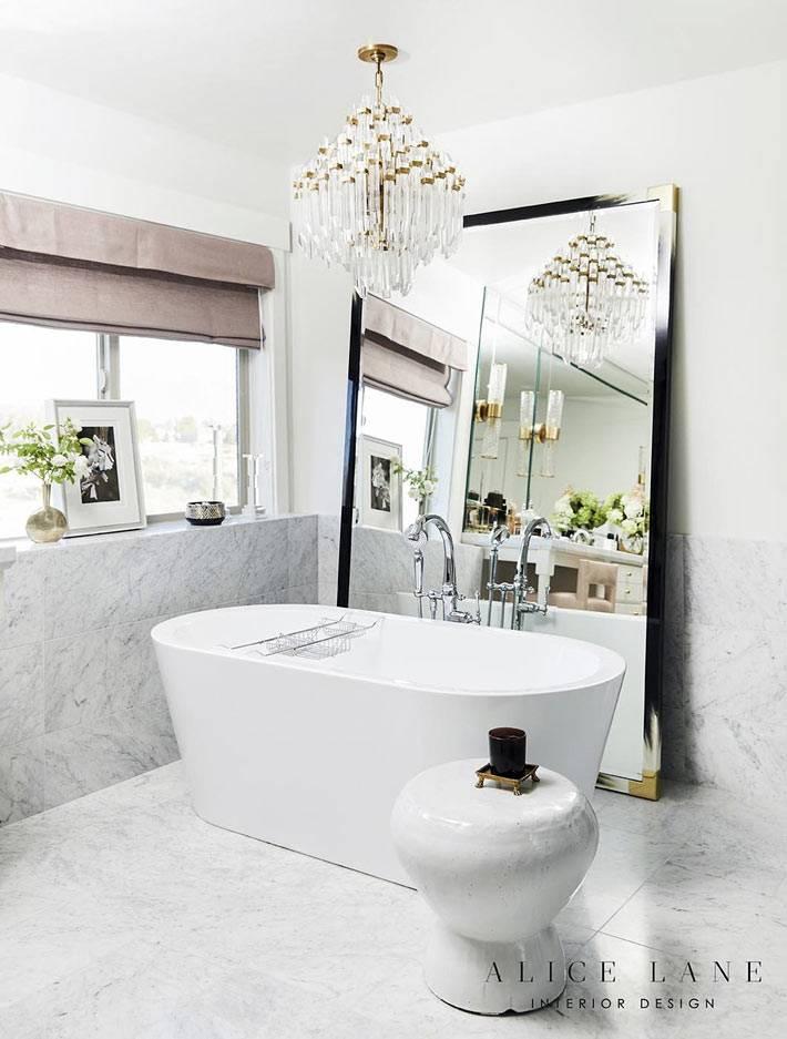 большое окно, напольное зеркало и люстра в ванной комнате фото