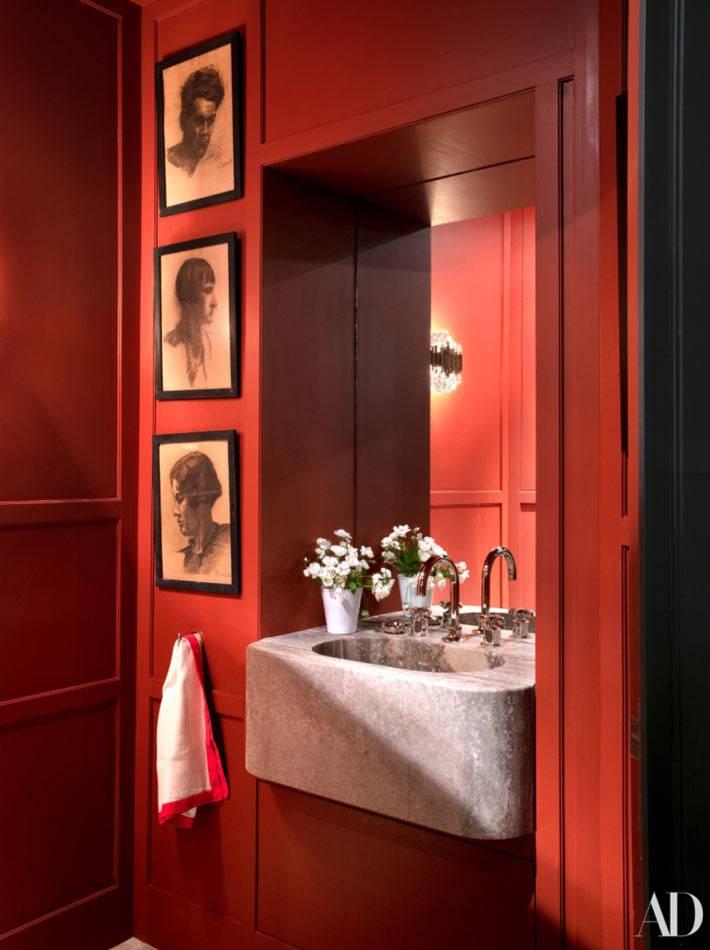 ванная комната с красными стенами и портретами