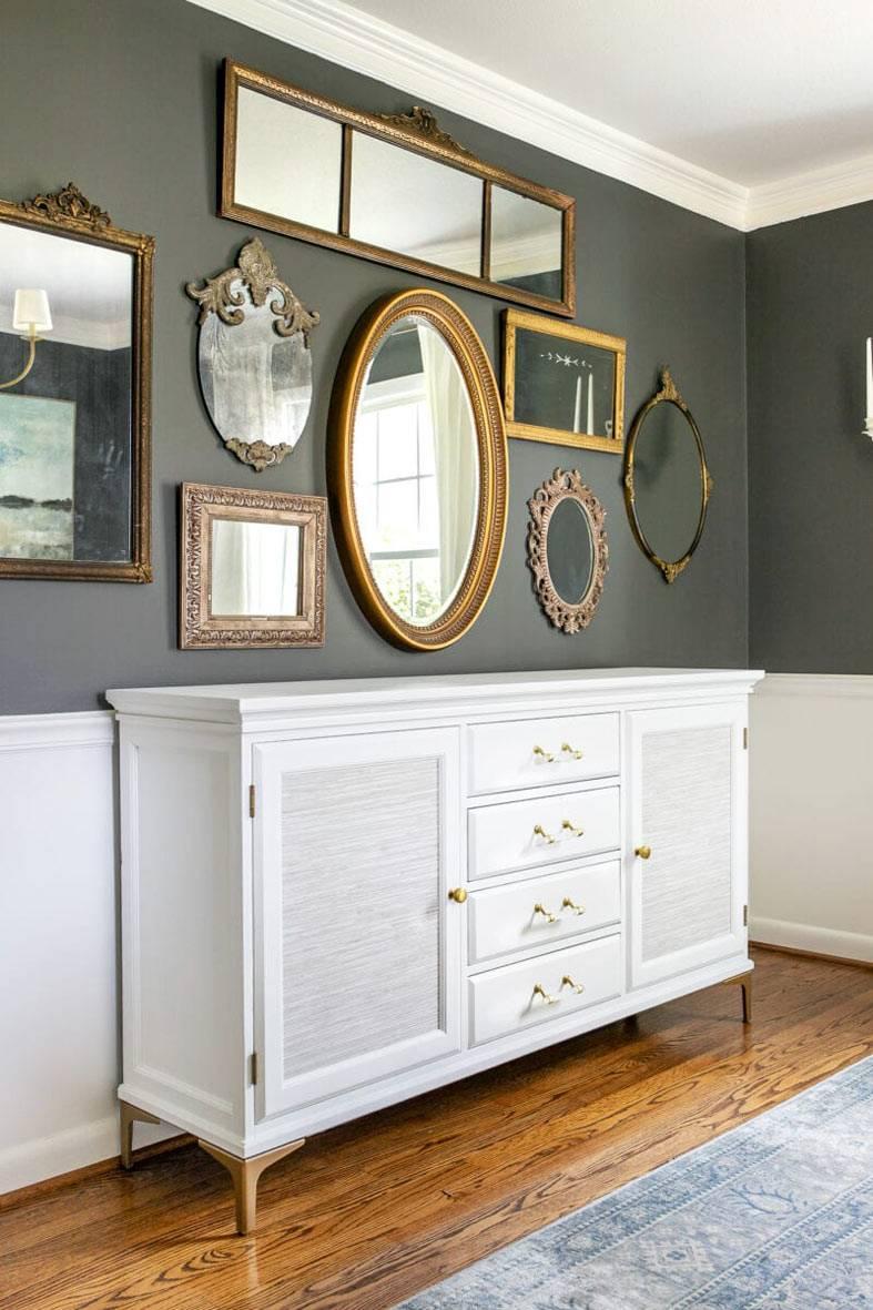 зеркала с золотистых рамах на серой стене, белый комод