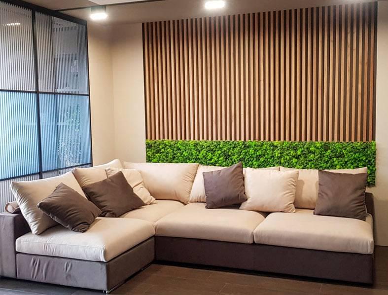 небольшая гостиная с диваном, рейки из дерева на стене