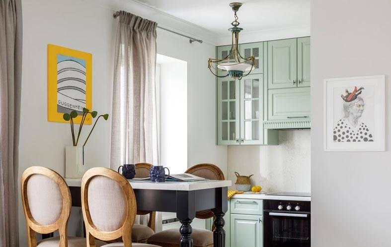 пастельно оливковая кухня с черным обеденным столом фото