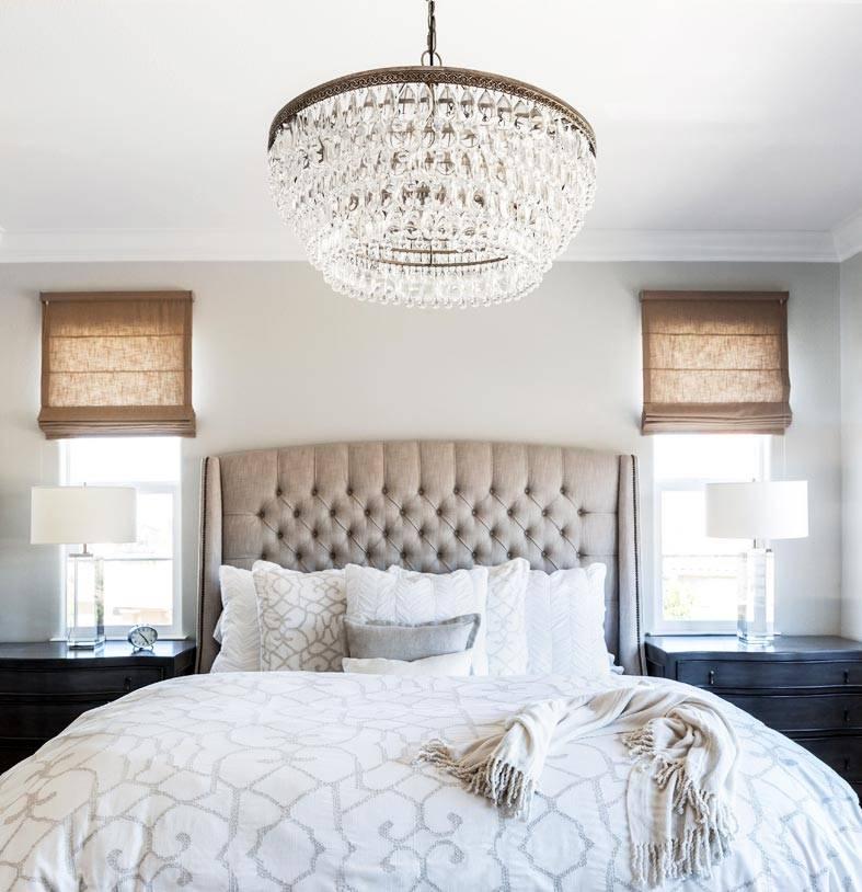 большая кровать между двумя окнами с римскими шторами