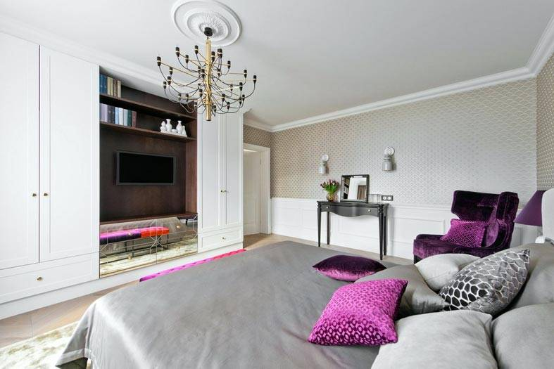 большой интерьер спальни с телевизором напротив кровати