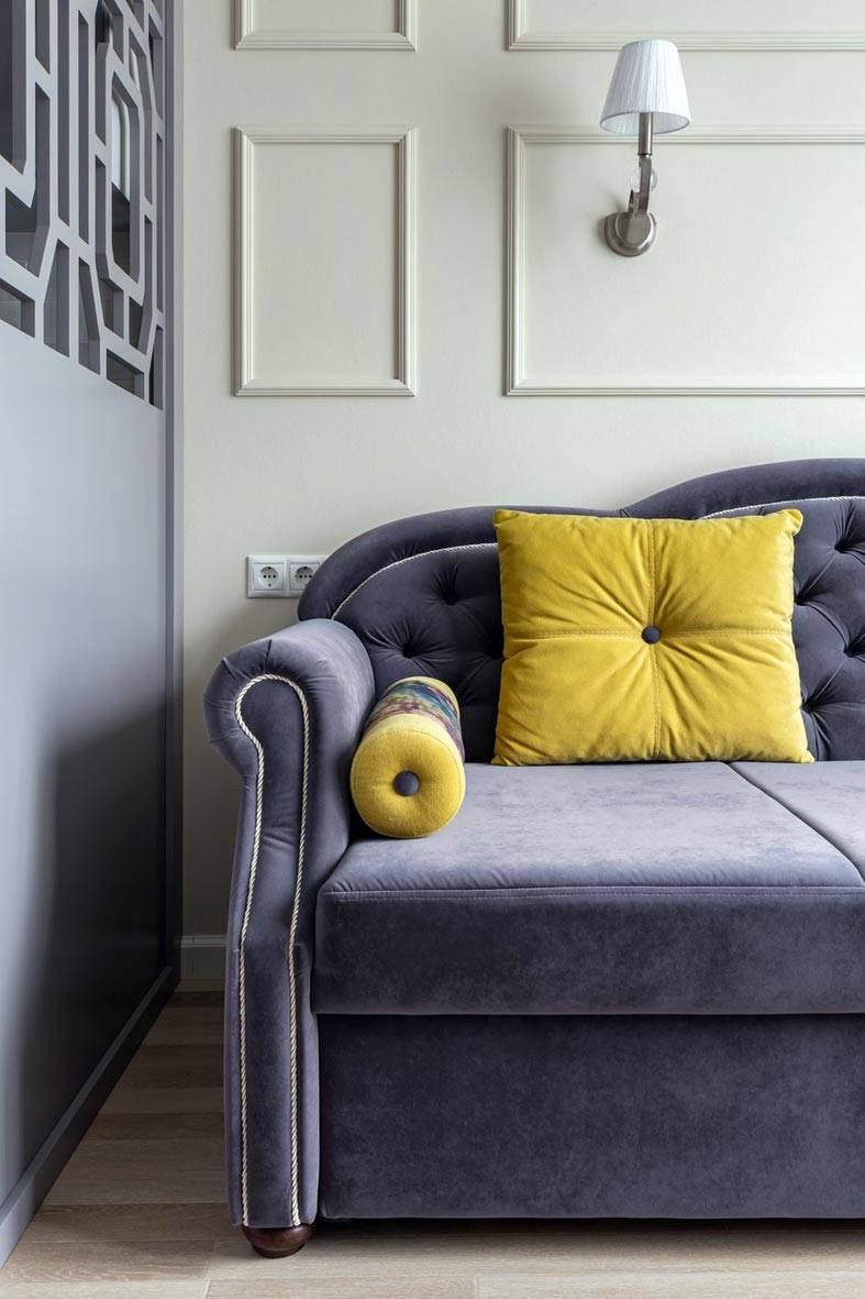 молдинги на стенах над серым диваном с желтыми подушками