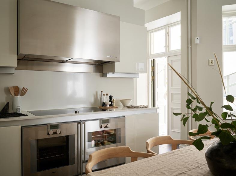 открытая кухня со светлой мебелью, большая вытяжка