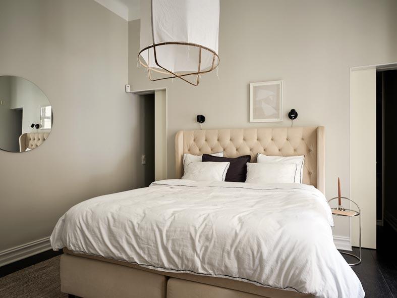 кровать с мягким бежевым изголовьем, круглое зеркало
