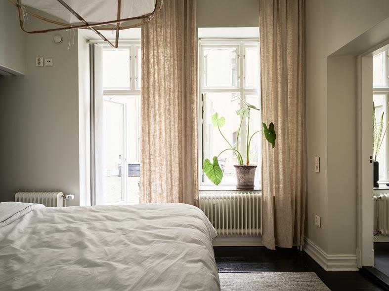 высокие потолки в спальне, комнатное растение на подоконнике