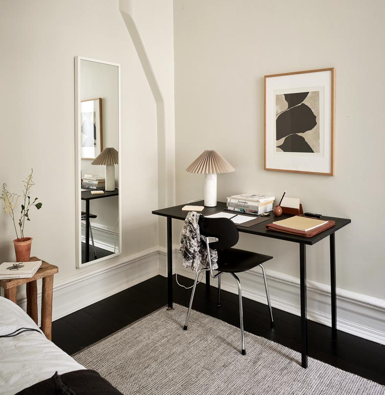 черный письменный стол, настенное зеркало в белой раме