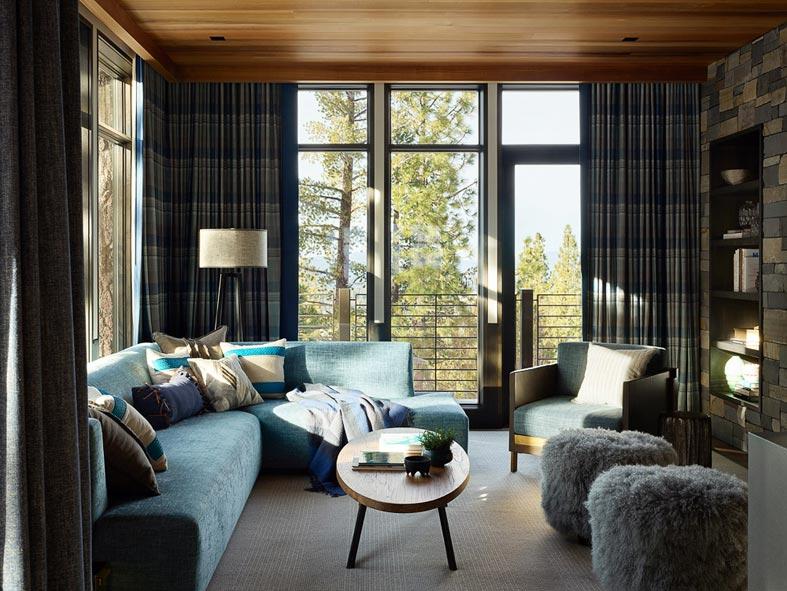 синий угловой диван в комнате для отдыха фото