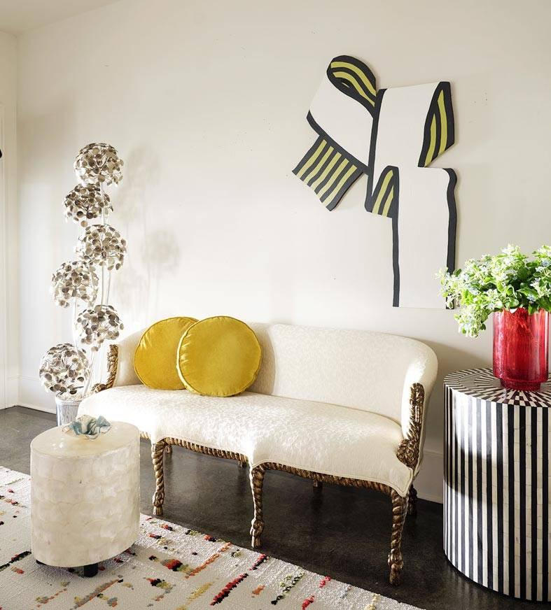 белый винтажный диванчик на ножках с желтыми подушками