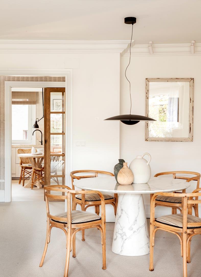 белый круглый мраморный стол и деревянные стулья