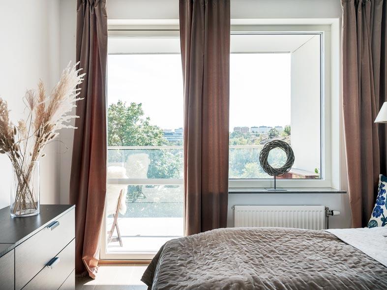 уютная спальня с балконом,коричневые шторы на окнах