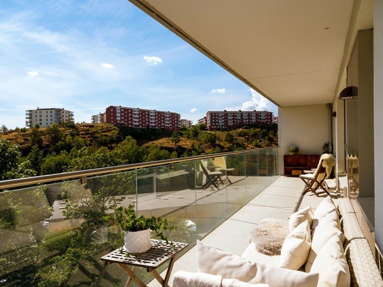огромный балкон открытого типа с мягким диваном и креслами