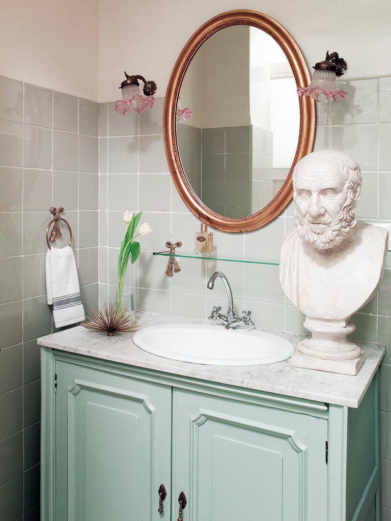 оливковая ванная комната с винтажными бра и гипсовым бюстом