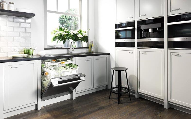 раковина перед окном в красивой белой кухне фото