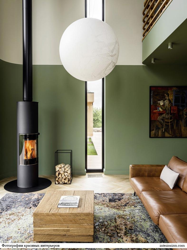 кожаный диван, круглый камин с трубой черного цвета